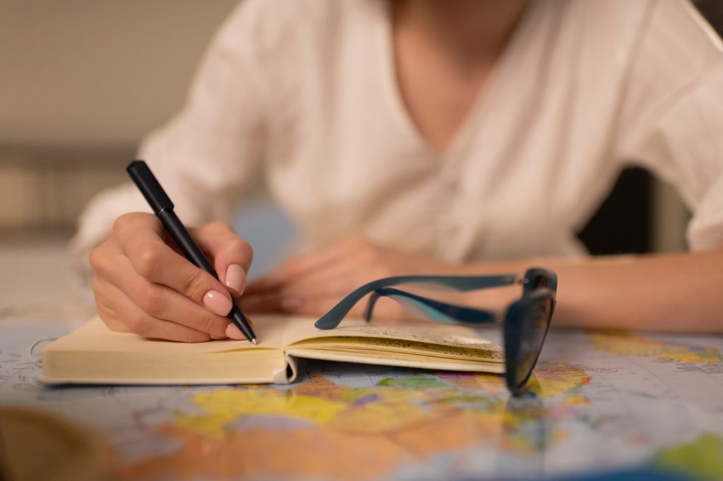 Anonymous female writing trip route in notepad