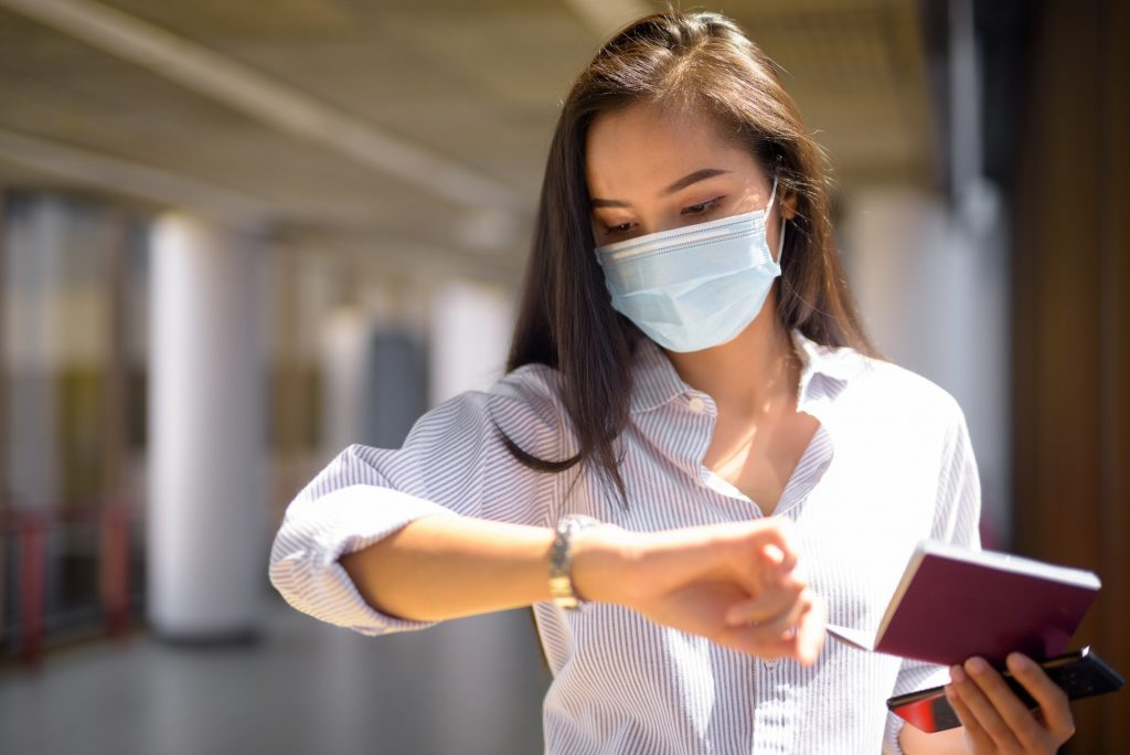 Young Asian tourist woman with mask checking time while holding passport at the airport